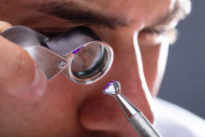 Jeweler Looking At Diamond Inclusions